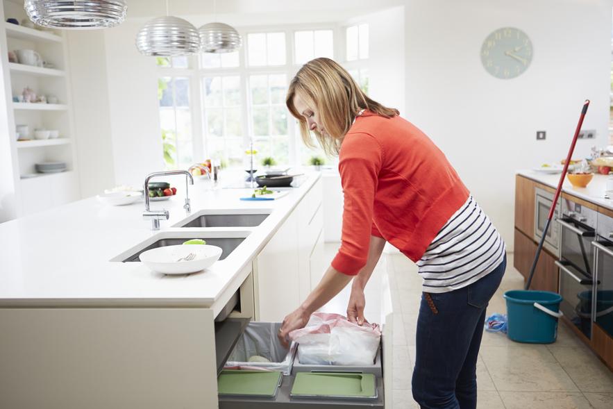 Woman Standing In Kitchen Emptying Waste Bin